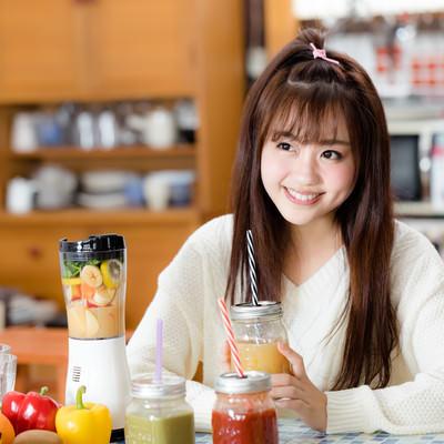 「台所でスムージーを飲む女性」の写真素材